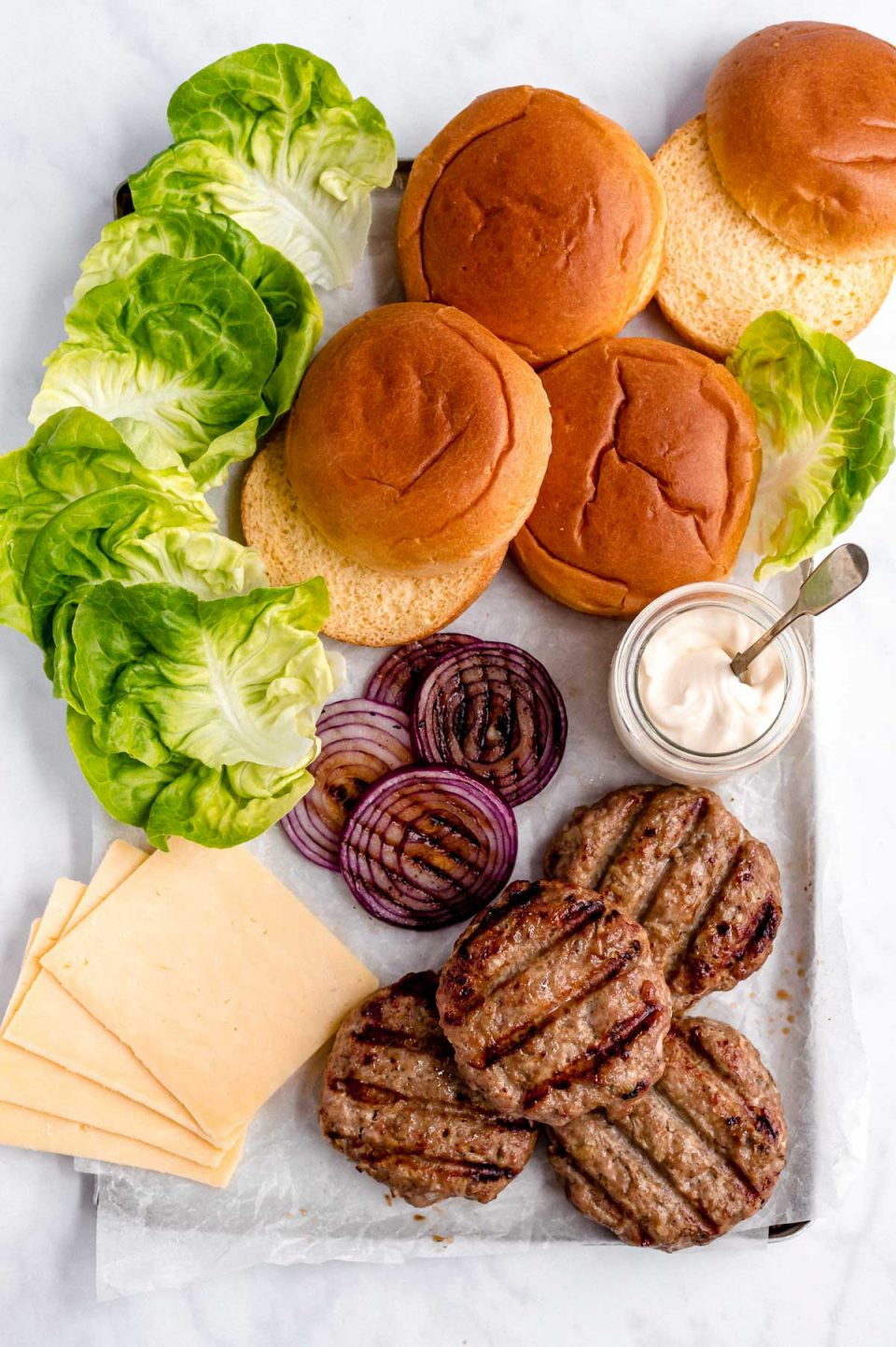 Grilled turkey burgers arranged on a platter with toppings - sliced cheese, leaf lettuce, grilled red onions & a jar of burger sauce.