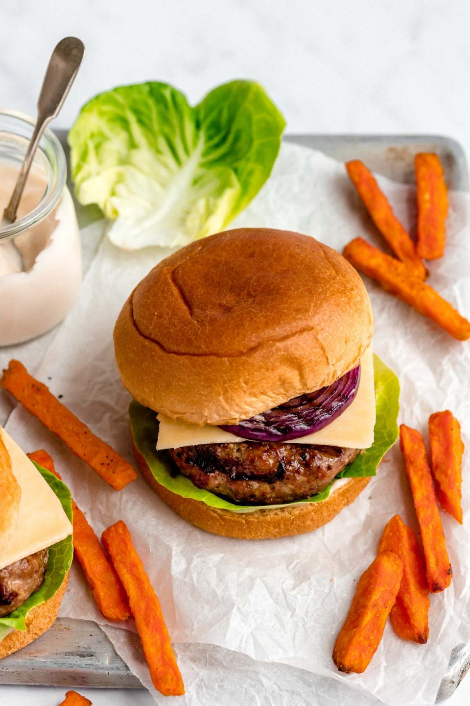 A grilled turkey burger served in a burger bun with lettuce, cheese & grilled red onion. Surrounding the burgers are sweet potato fries, & a small jar of burger sauce.