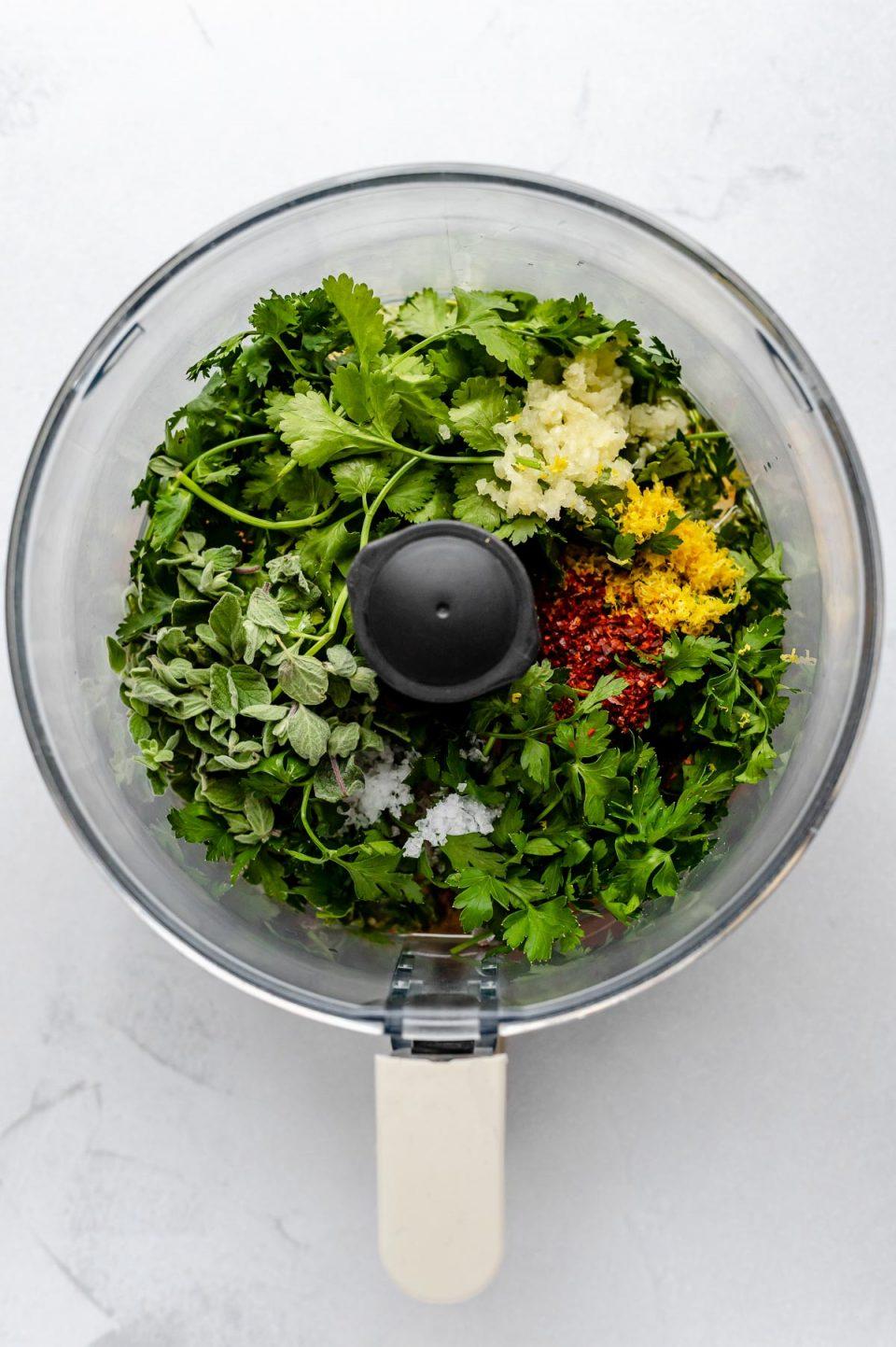 Easy Chimichurri sauce recipe ingredients fill up a food processor bowl: cilantro, parsley, oregano, garlic, lemon juice & zest, olive oil, red wine vinegar, crushed red pepper flakes, and kosher salt.