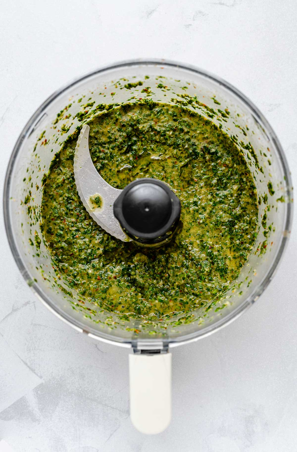 A top down photo of easy Chimichurri sauce that has been pulsed in a food processor bowl. The bowl sits on a light gray surface.