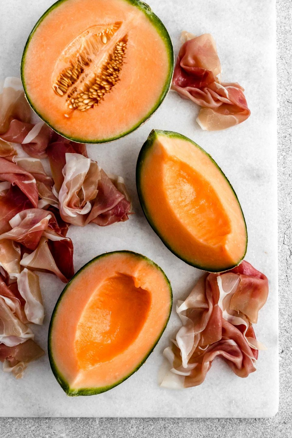 Cantaloupe melon and thinly sliced prosciutto on a white cutting board. The cantaloupe is sliced, half with seeds still in it & half deseeded.