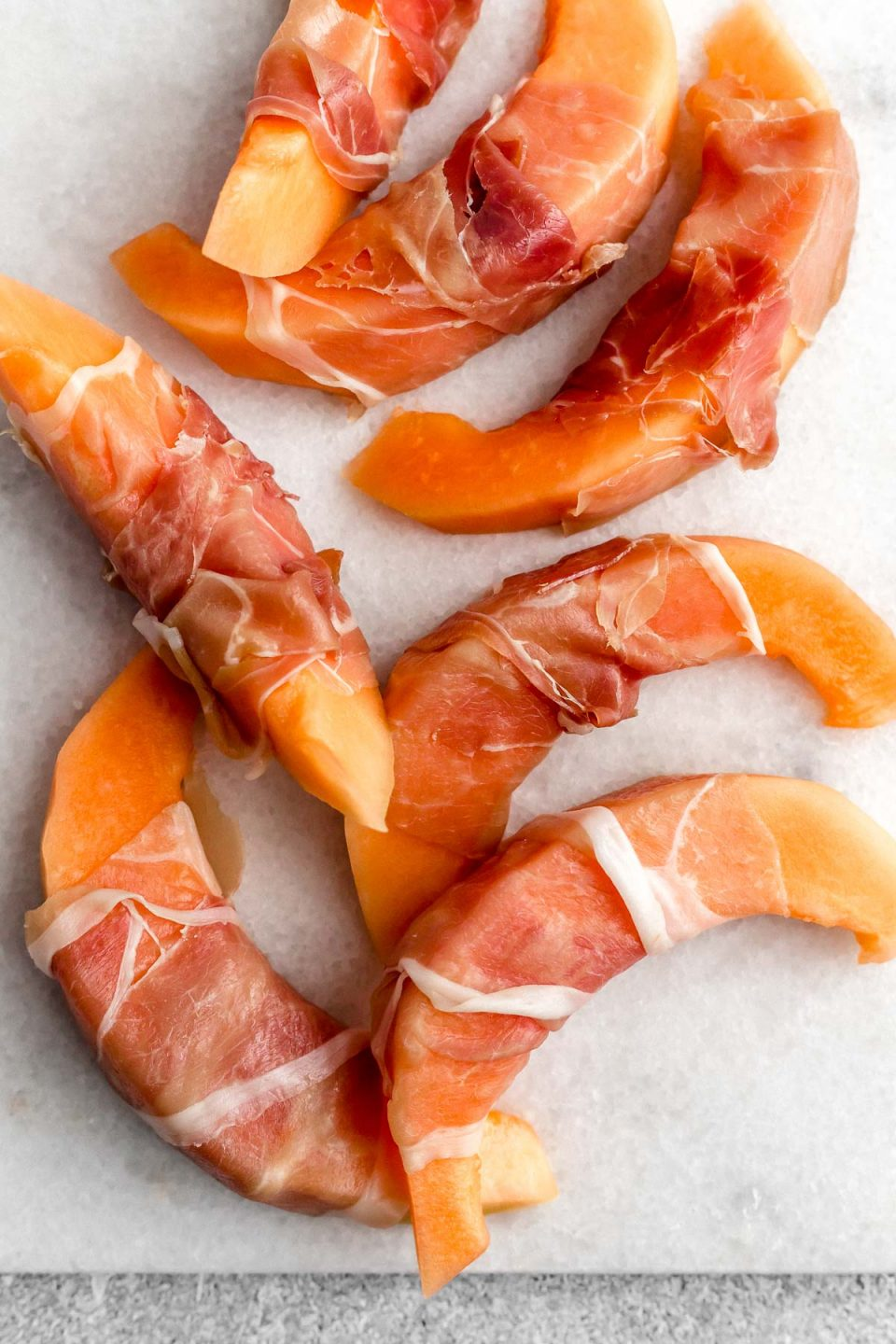 Thinly sliced prosciutto wrapped around 7 cantaloupe melon spears. The Prosciutto-wrapped cantaloupe sit atop a white cutting board.