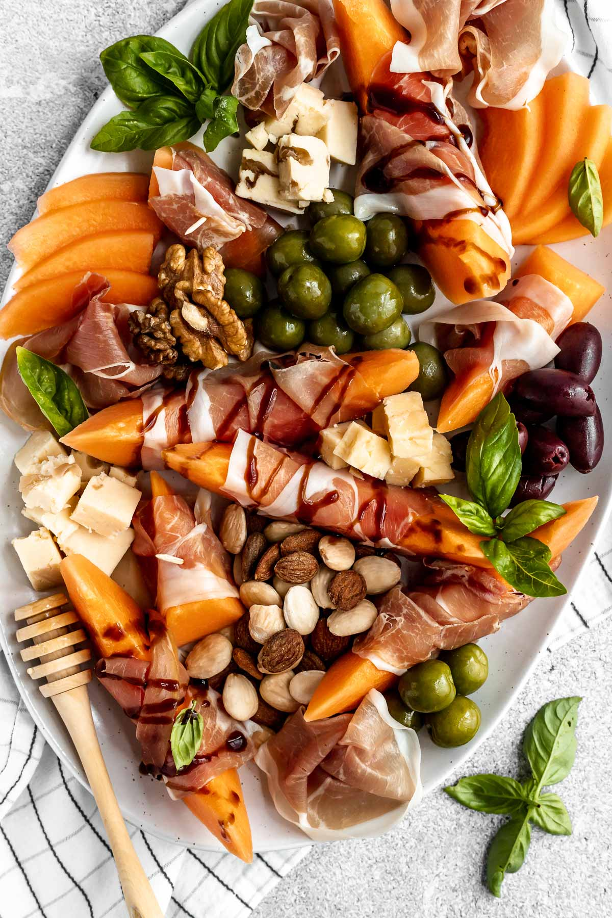 Close up of prosciutto and melon cheese board! Prosciutto-Wrapped Cantaloupe on a large serving platter with olives, nuts, cheese, & fresh basil leaves. Some pieces of prosciutto-wrapped melon are drizzled with balsamic syrup.