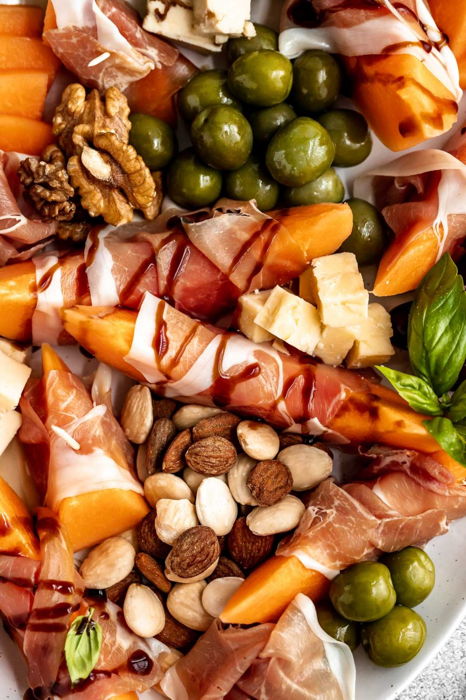 Even closer close up of prosciutto and melon cheese board! Prosciutto-Wrapped Cantaloupe on a large serving platter with olives, nuts, cheese, & fresh basil leaves. Some pieces of prosciutto-wrapped melon are drizzled with balsamic syrup.