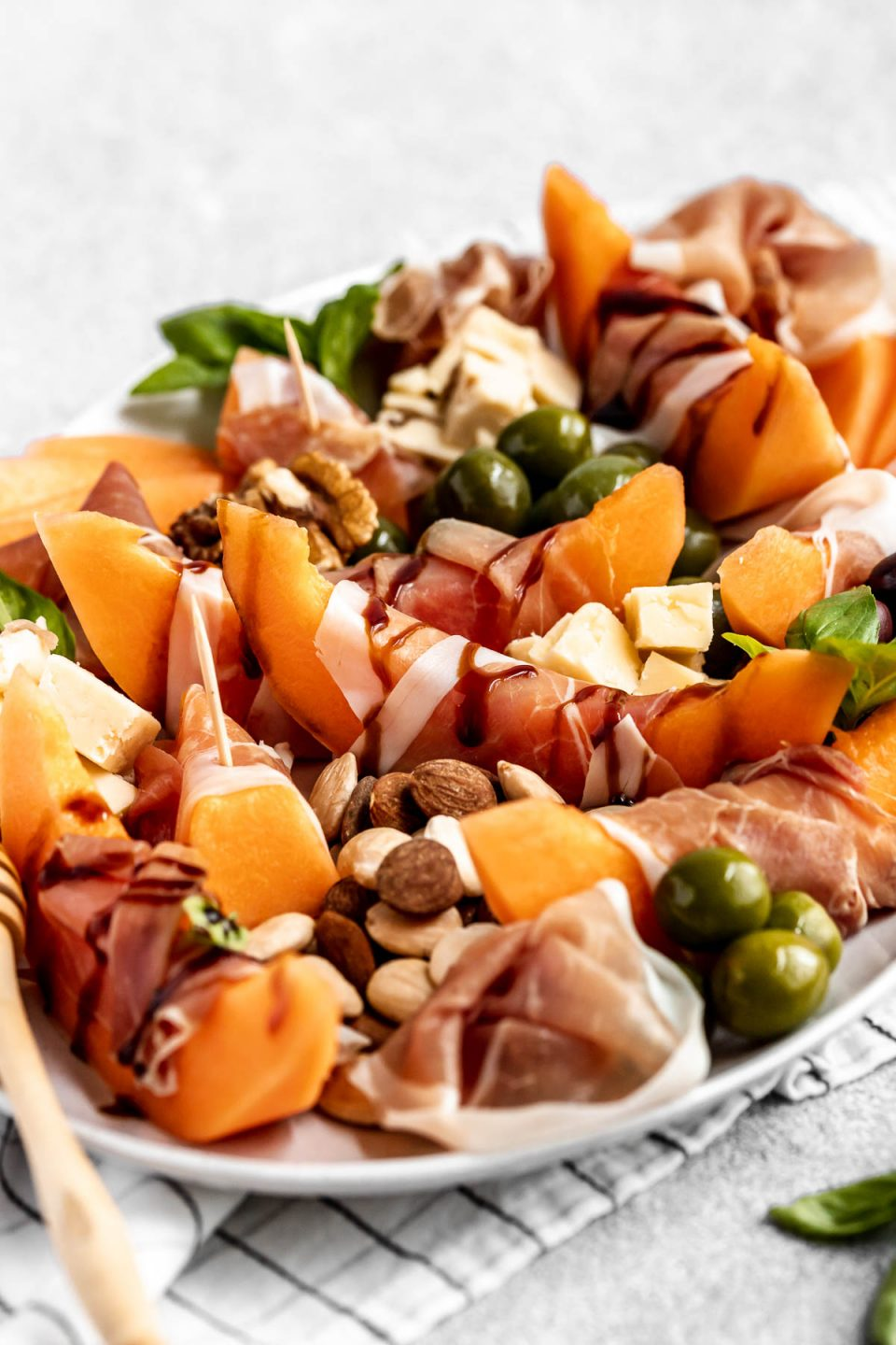 Side angle of prosciutto and melon cheese board! Prosciutto-Wrapped Cantaloupe on a large serving platter with olives, nuts, cheese, & fresh basil leaves. Some pieces of prosciutto-wrapped melon are drizzled with balsamic syrup.