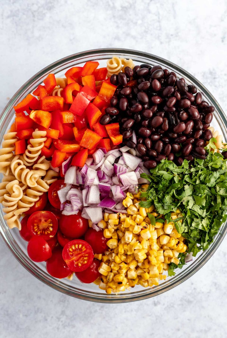 Vegan Southwest Pasta Salad ingredients arranged in a large, glass mixing bowl: spiral pasta, chopped red bell pepper, black beans, diced red onion, fire-roasted corn, halved cherry tomatoes, & freshly chopped cilantro. The bowl sits atop a light blue surface.