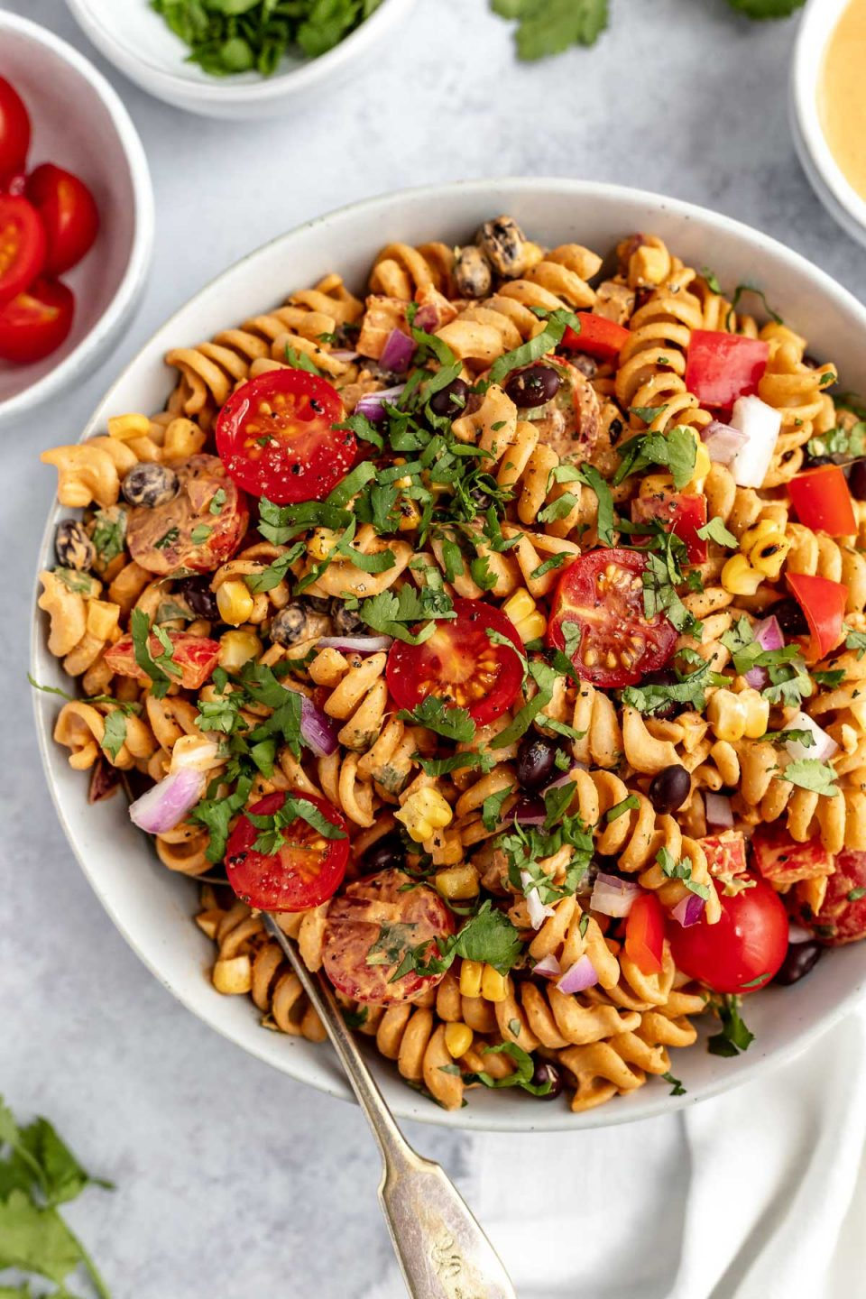 Creamy Vegan Southwest Pasta Salad shown in a large white serving bowl. The salad is garnished with freshly chopped cilantro. The bowl is placed on a light blue surface, surrounded with smaller white dishes filled with tomatoes, chopped cilantro, & creamy vegan southwest dressing.