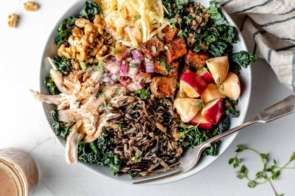A large white bowl filled with autumn grain bowl ingredients: shredded kale, wild rice, quinoa, apple, roasted sweet potato, diced red onion, shredded cheese, chopped walnuts & shredded chicken. A fork is placed in the grain bowl, nestled to the left side under the wild rice & quinoa. The bowl sits atop a light blue surface, surrounded by sprigs of fresh thyme & a striped linen napkin. Next to the bowl are some whole walnuts & a jar of maple balsamic dressing.