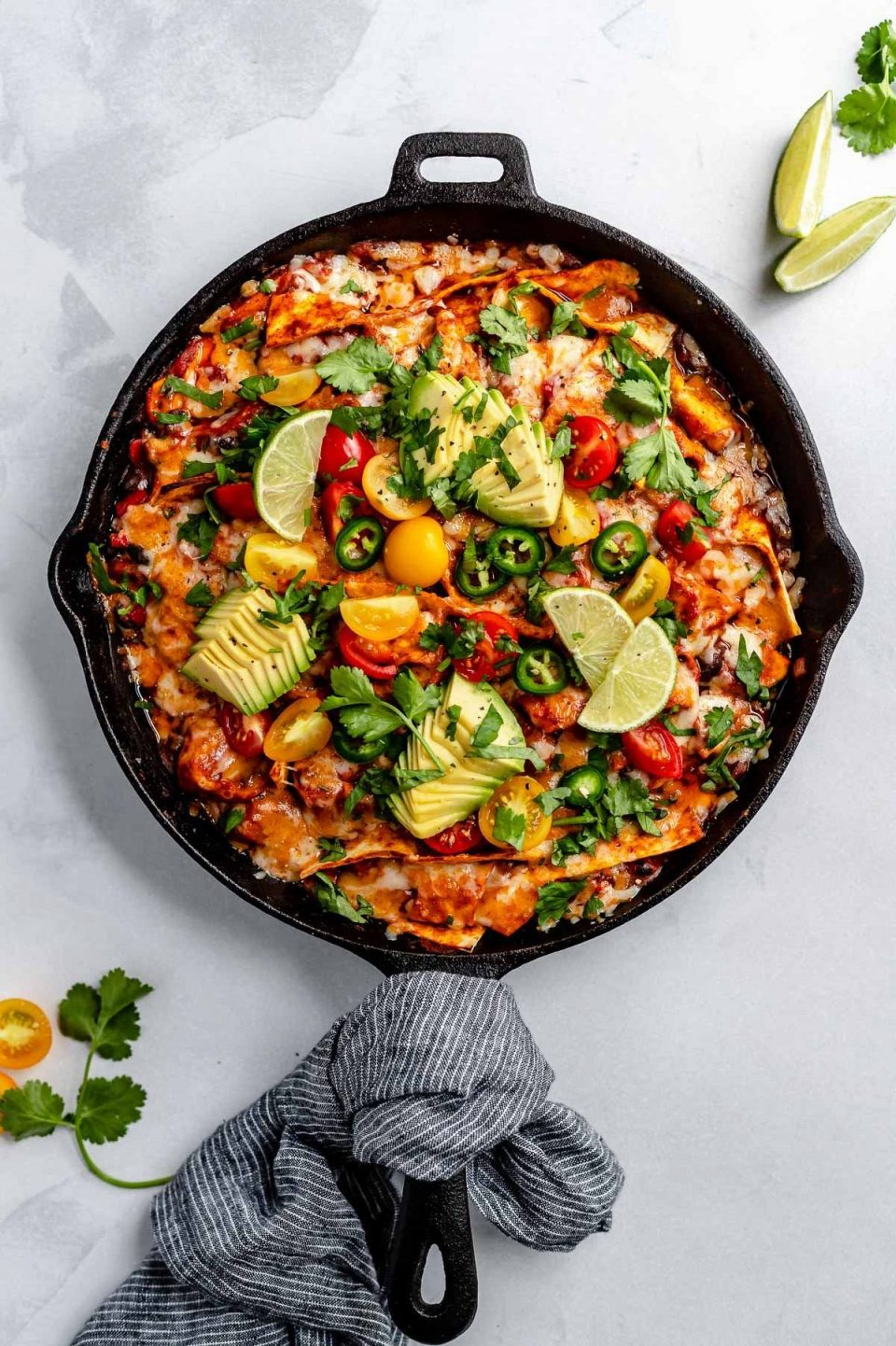 Vegetarian skillet enchiladas, shown in a large black skillet, topped with melted cheese, cherry tomatoes, sliced avocado, roughly chopped cilantro, thinly sliced jalapeno pepper. The skillet sits atop a light blue surface, with its handle wrapped in a black & white linen napkin. Next to the skillet, on the surface, are cilantro leaves & lime wedges for serving.