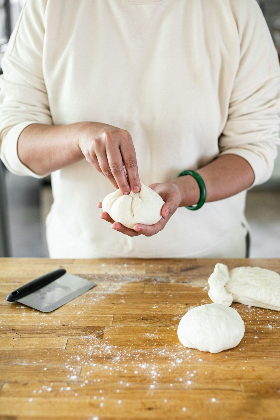 How to shape pizza dough balls: Jess, shown in a white sweatshirt, stands behind a butcher block counter dusted in flour. Jess is pinching the bottom of the pizza dough ball together.