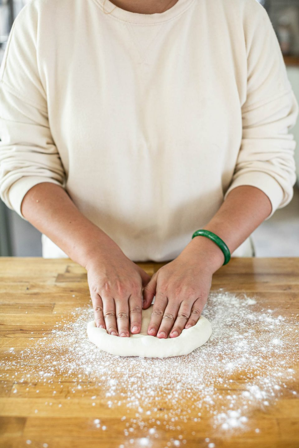 How to form pizza crust: Jess, shown in a white sweatshirt, stands behind a butcher block counter dusted in flour. Jess' fingers are pressed into a pizza dough ball, forming it into crust.