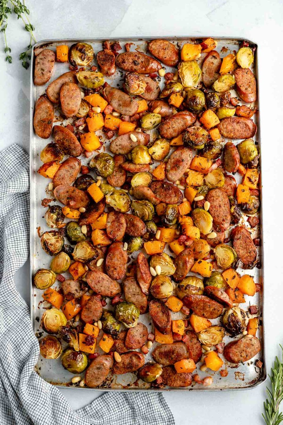 Sheet pan chicken sausage & vegetables. Thinly sliced chicken sausage, diced butternut squash, & halved brussels sprouts are browned & roasty on a large sheet pan. The chicken sausage sheet pan sits atop a light blue surface with a striped linen napkin.