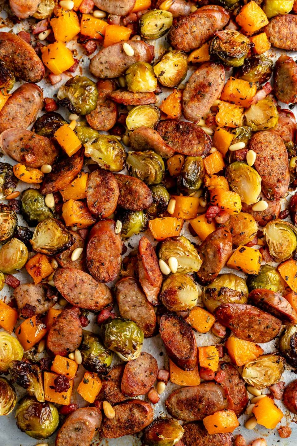 Sheet pan chicken sausage & veggies after roasting - the sliced chicken sausage, diced butternut squash, & halved brussels are deeply browned & roasty. The sheet pan is topped with a sprinkling of pine nuts.