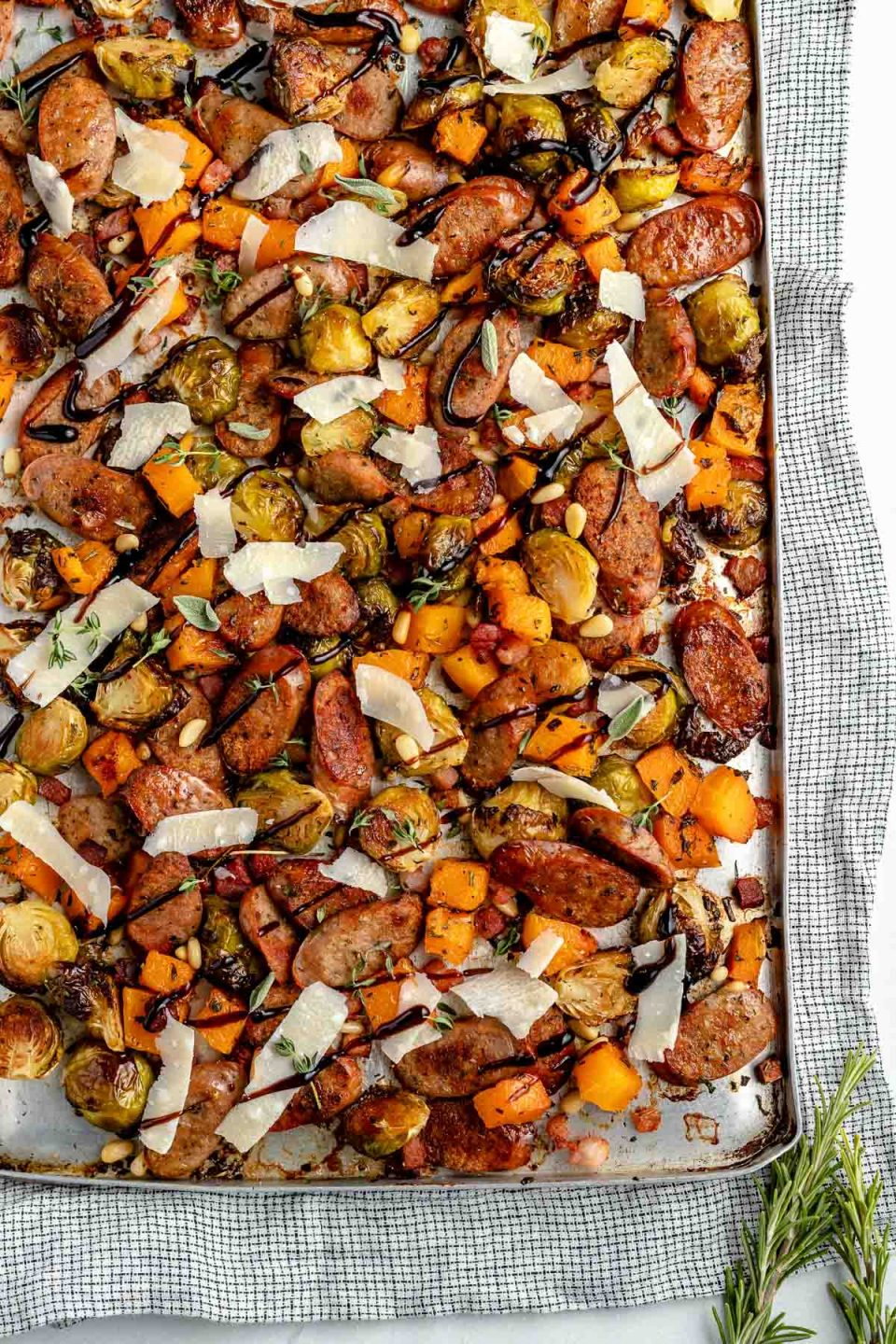 Sheet pan chicken sausage & vegetables. Thinly sliced chicken sausage, diced butternut squash, & halved brussels sprouts are browned & roasty on a large sheet pan, & topped with grated parmesan & a drizzle of balsamic glaze. The chicken sausage sheet pan sits atop a light blue surface with a striped linen napkin.