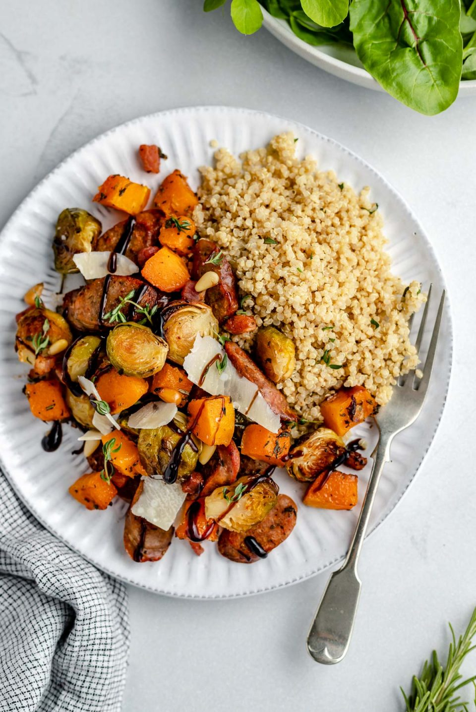 Roasted chicken apple sausage, butternut squash & brussels sprouts with quinoa on a white plate. The chicken sausage & veggies are topped with parmesan, a drizzle of balsamic glaze, & a sprinkling of fresh herbs. The plate sits atop a light blue surface next to a gray striped linen napkin.