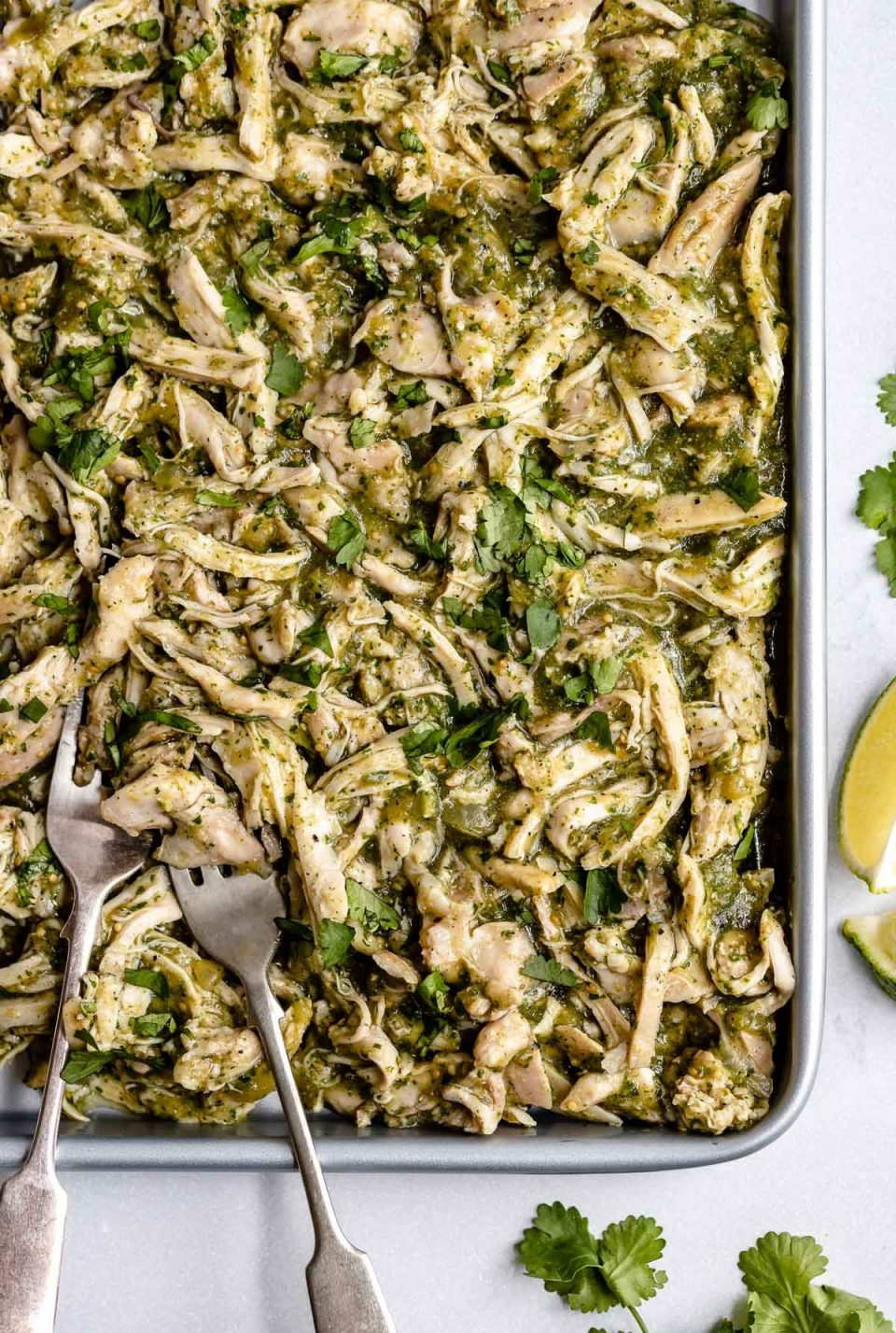 Shredded Salsa Verde Chicken (Pollo Verde) shown on a large sheet pan. 2 forks, used for shredding, are nestled to the chicken on the sheet pan. The sheet pan sits atop a light blue surface. Placed around the sheet pan are cilantro leaves & lime wedges.