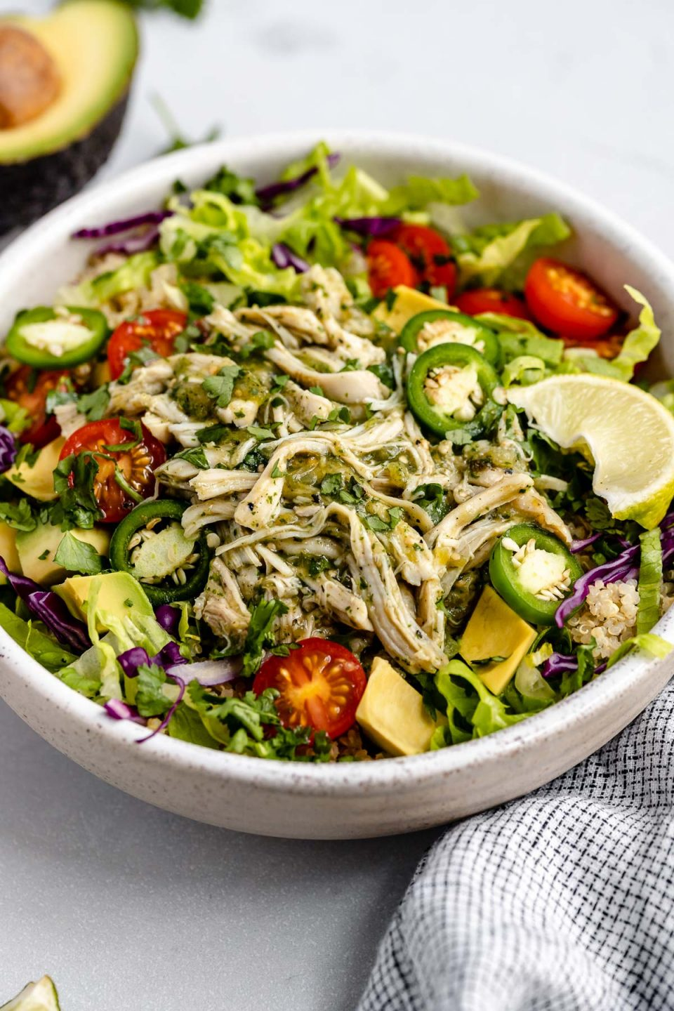 Side angle of shredded salsa verde chicken (pollo verde) shown in a large burrito bowl, made with quinoa, lettuce, cabbage, tomatoes, avocado & jalapeno. The bowl sits atop a light blue surface, next to a checkered blue linen, a halved avocado, cilantro leaves & a lime wedge.