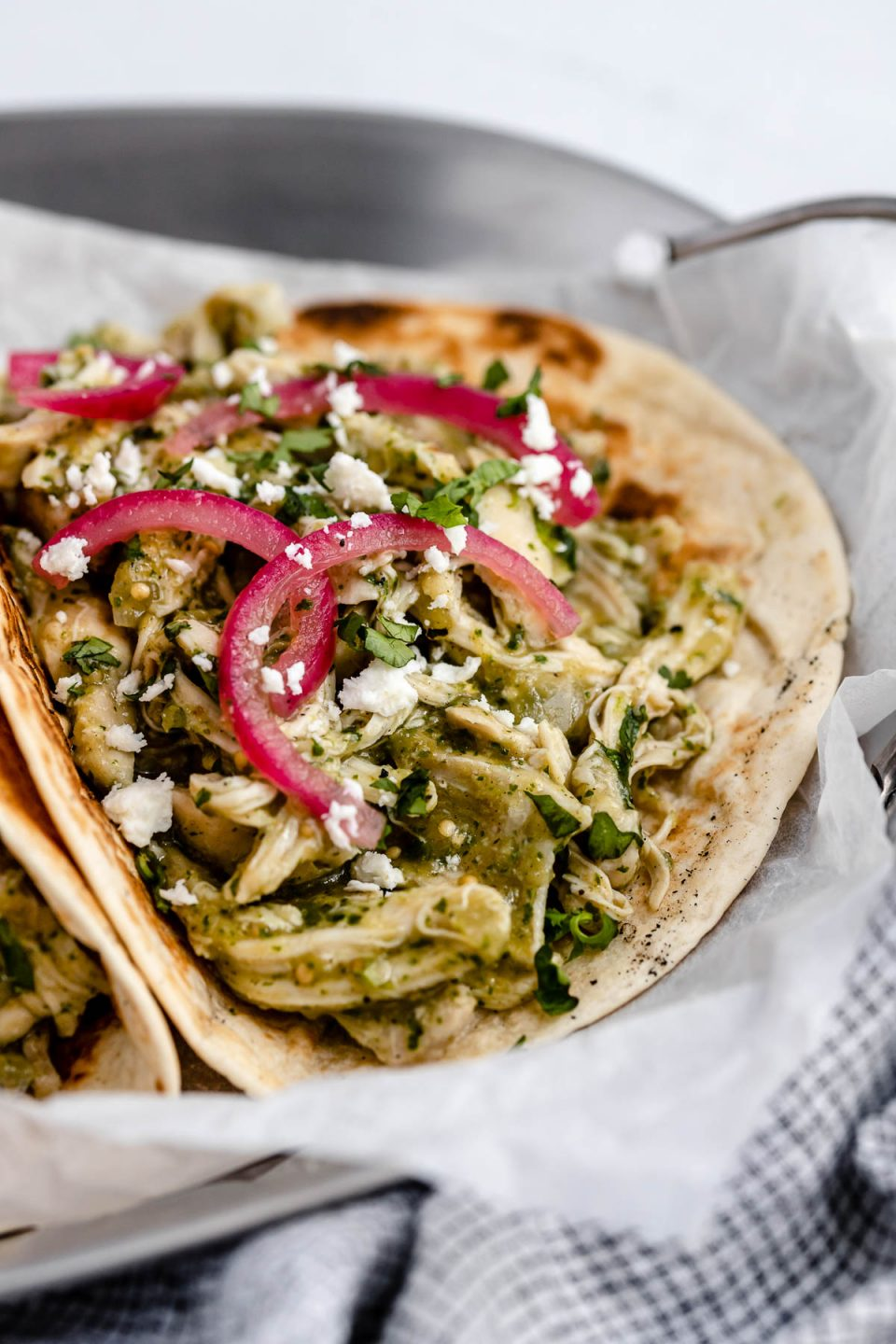 Side angle of salsa verde chicken (pollo verde) taco, topped with chopped cilantro and pickled red onions, placed on a metal tray with handles. The tray sits atop a light blue surface, next to a checkered blue linen napkin.