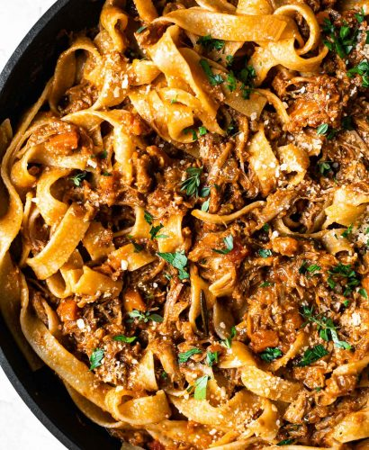Close up of pork shoulder ragu tossed into pappardelle pasta in a skillet. The pasta is topped with fresh herbs.