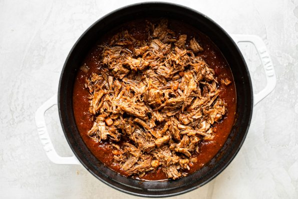 Shredded pork shoulder in tomatoey ragu sauce in a large white Dutch oven.
