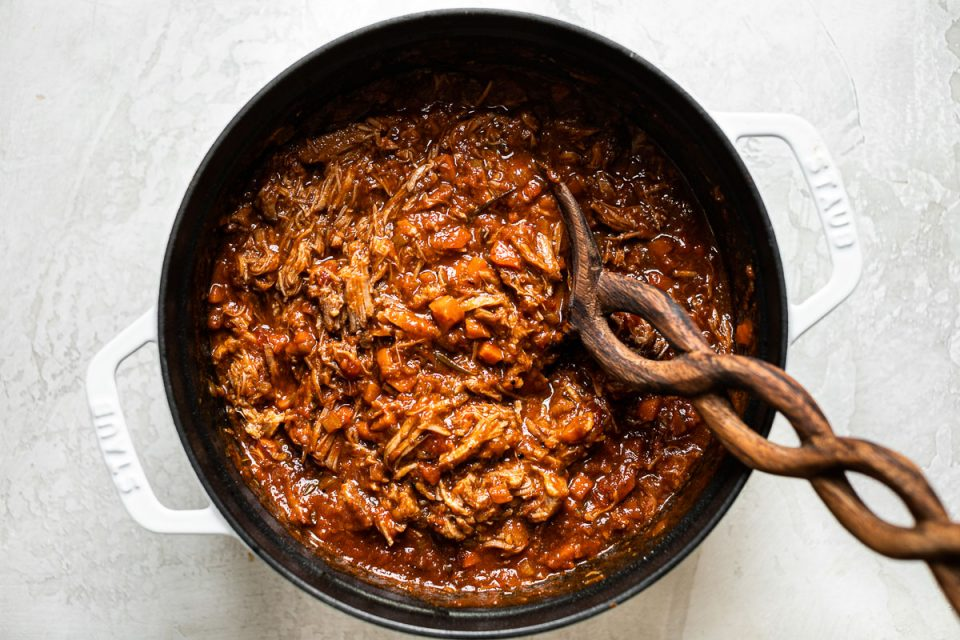 Overhead view of pork shoulder ragu shown in a large white Dutch oven, with a wooden spoon nestled into the pot.