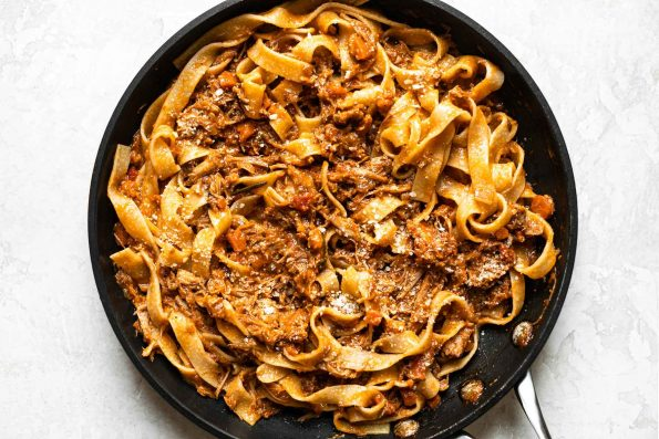 Braised pork ragu tossed into pappardelle pasta in a skillet.
