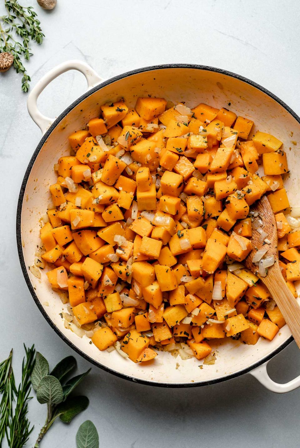Sauteeing butternut squash in a large skillet with onion, sage, & garlic. A wooden spoon is nestled into the squash. The skillet sits atop a light blue surface, next to fresh herbs & whole nutmeg.