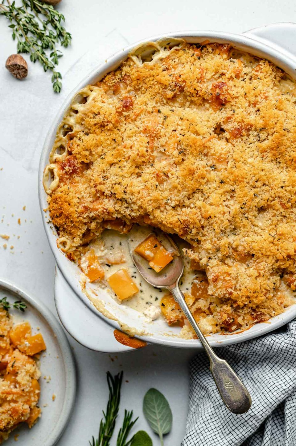 Baked butternut squash au gratin in a round baking dish. A spoonful of gratin has been taken out of the baking dish. The baking dish sits atop a light blue surface, next to a checkered linen napkin, fresh herbs & whole nutmeg.