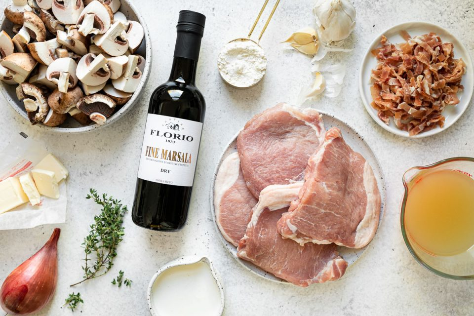 Pork marsala ingredients arranged on a white surface: mushrooms, butter, shallot, fresh thyme, a bottle of Florio Fine Marsala wine, flour, garlic, pork chops, prosciutto, chicken stock & heavy cream.