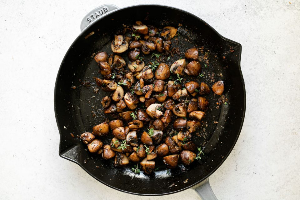 Caramelized mushrooms garnished with fresh thyme in a large gray Staub skillet. The skillet sits atop a white surface.