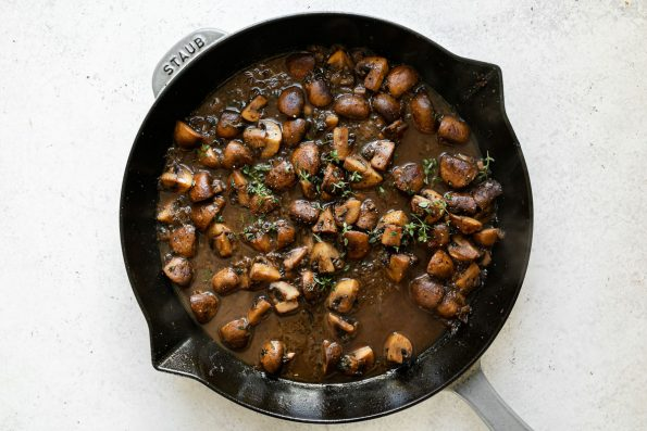 Caramelized mushrooms in marsala sauce in a large grey Staub skillet. The skillet sits atop a white surface.