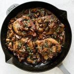 Pork marsala with mushrooms & creamy marsala sauce in large gray Staub skillet. The pork chops are topped with caramelized mushrooms, crispy prosciutto & fresh thyme. The skillet sits atop a white surface.