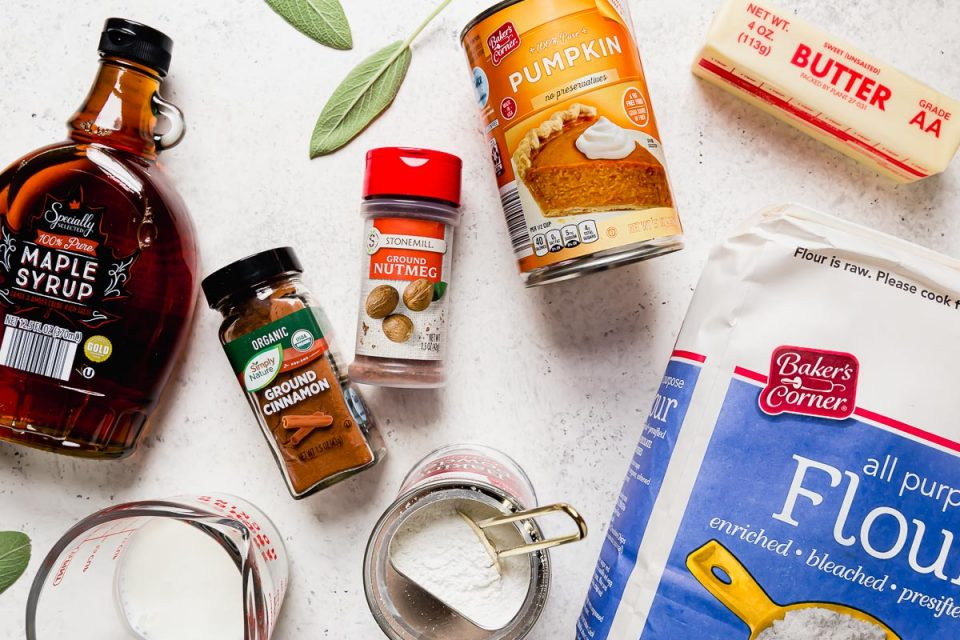 Pumpkin biscuits ingredients arranged on a white surface: Specially Selected Maple Syrup, buttermilk, Simply Nature Organic Ground Cinnamon, Stonemill Ground Nutmeg, baking powder, Baker's Corner Pumpkin, Baker's Corner Flour, & unsalted butter.