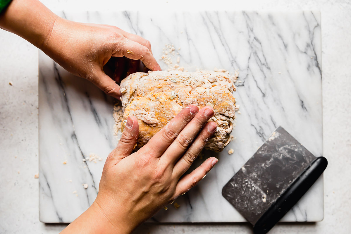 How to fold biscuit dough: A woman's hand shown holding a bench scraper, folding the pumpkin biscuit dough into thirds.