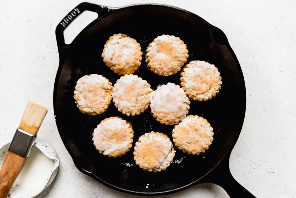 Pumpkin biscuits arranged in a Lodge cast iron skillet, topped with a brushing of buttermilk.