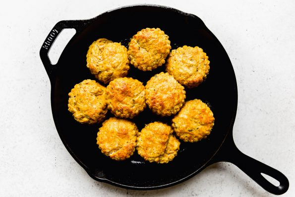 Baked pumpkin biscuits shown in a black Lodge skillet.