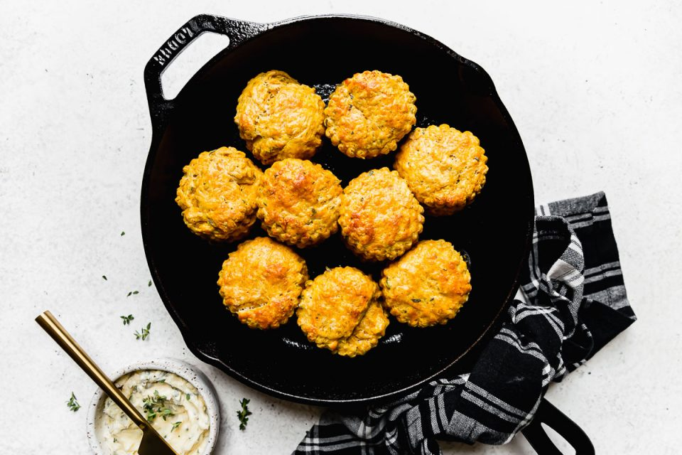 Baked pumpkin biscuits shown in a black Lodge skillet. The skillet sits atop a white surface, next to a ceramic bowl of garlic herb butter & a plaid black napkin.