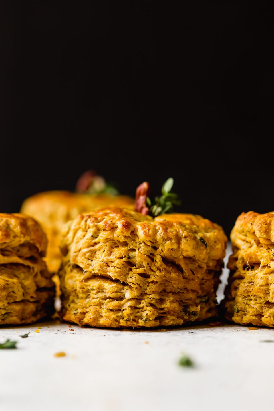Side angle of a row of pumpkin biscuits. The biscuits have a pecan & fresh herbs inserted in their tops, making the biscuits look like little pumpkins.