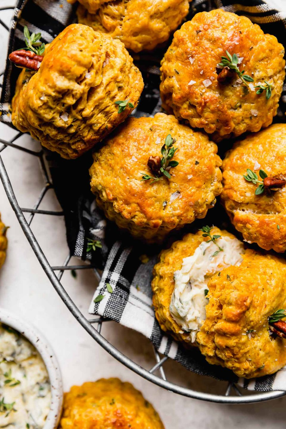Pumpkin biscuits, decorated like pumpkins with a pecan & fresh herbs inserted into the tops, shown in a wire basket lined with a black plaid napkin. The basket sits atop a white surface next to a small ceramic bowl with garlic herb butter.
