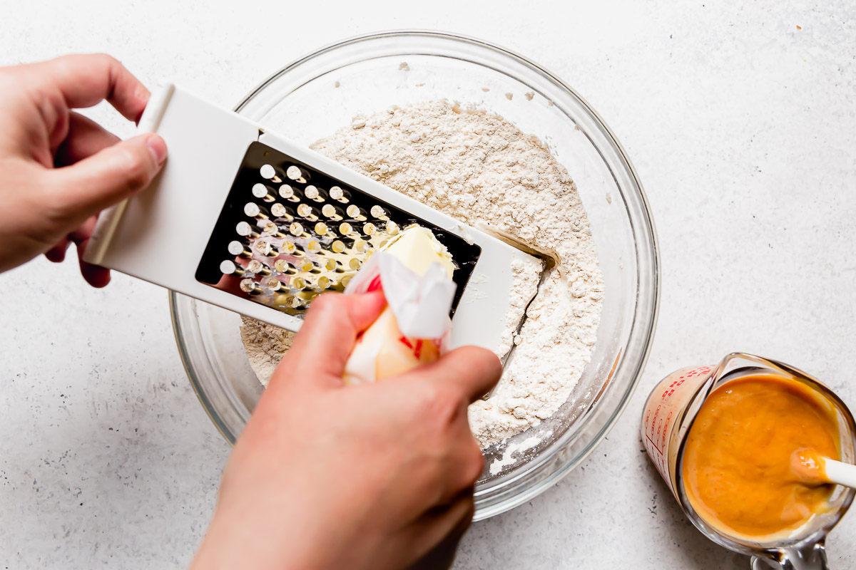 A woman's hands holding a box grater in dry ingredients, grating cold butter into the dry ingredients for homemade pumpkin biscuits.