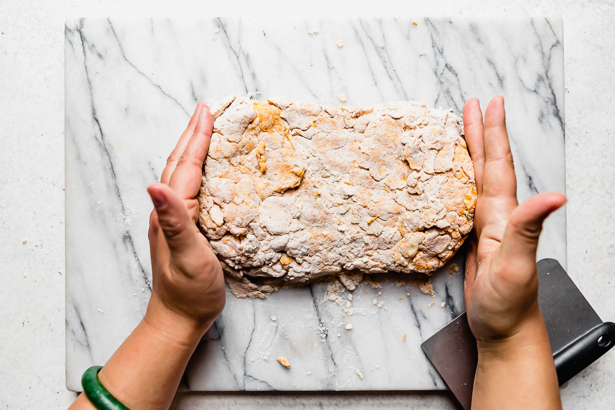A woman's hands shown shaping pumpkin biscuits dough into a large rectangle atop a white marble surface.