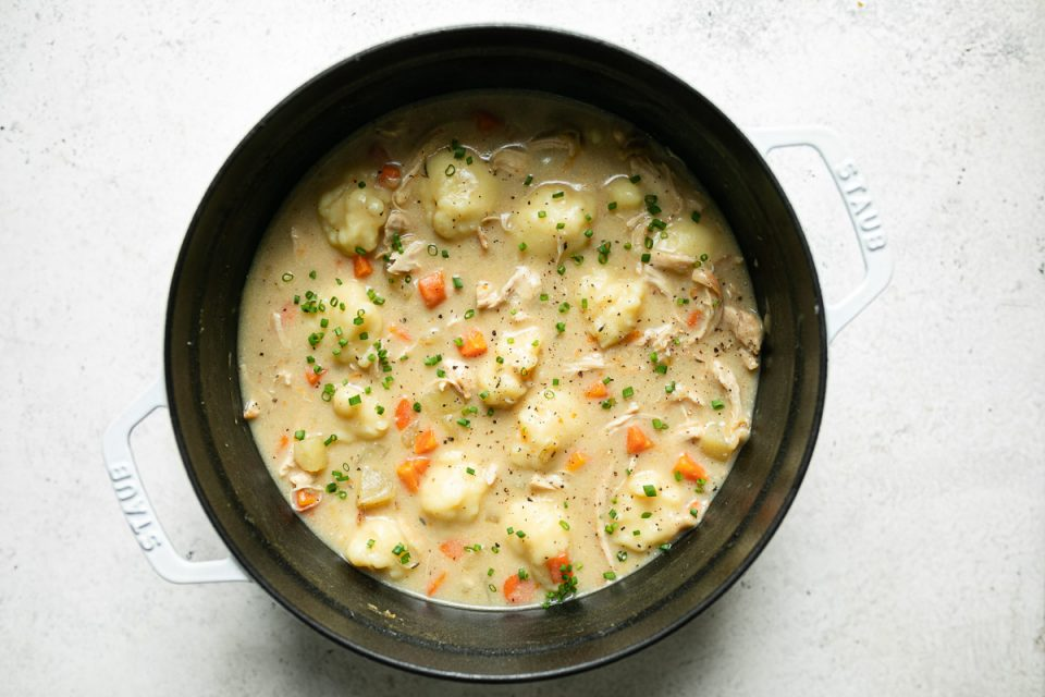 Italian chicken & gnocchi dumplings soup shown in white Staub dutch oven on a white surface. The soup is garnished with finely chopped fresh chives.