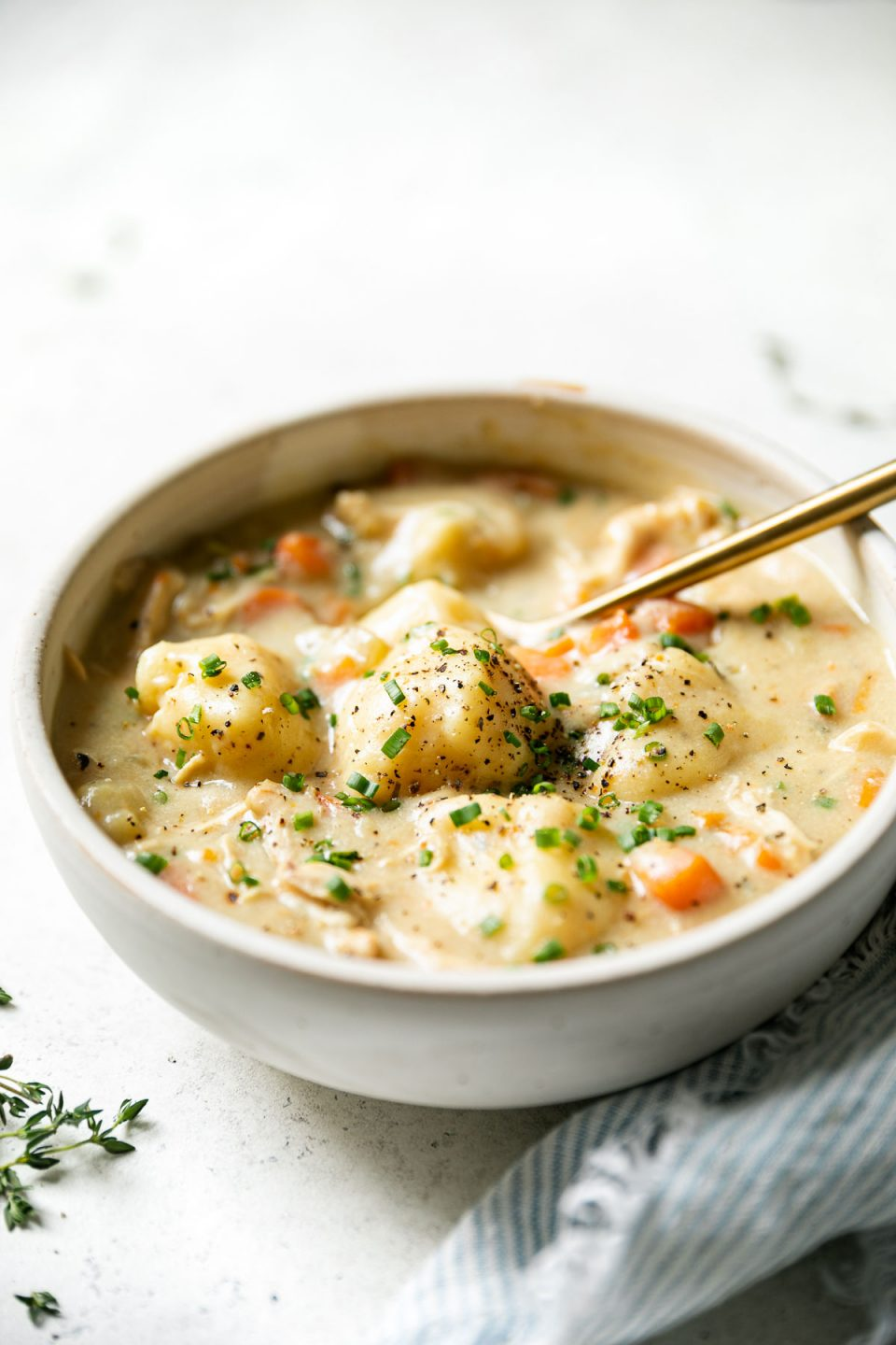 Side angle of bowl of Chicken & Gnocchi Soup, sitting atop a white surface, next to a blue & white striped linen napkin & a few sprigs of fresh thyme. The soup is garnished with cracked black pepper & finely chopped fresh chives & there is a gold spoon nestled in the bowl.