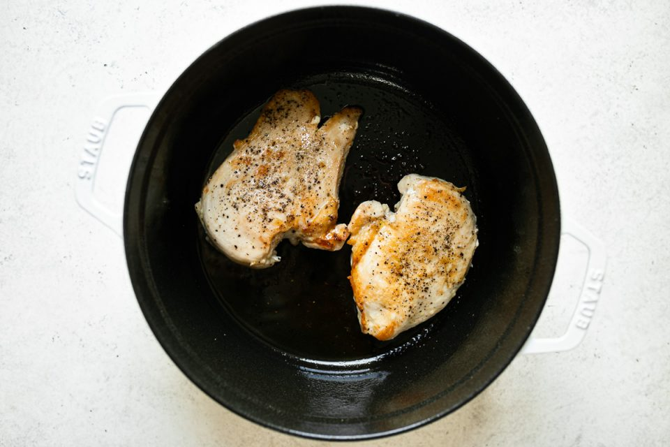 2 browned chicken breasts shown in a white Staub Dutch oven placed on a white surface.