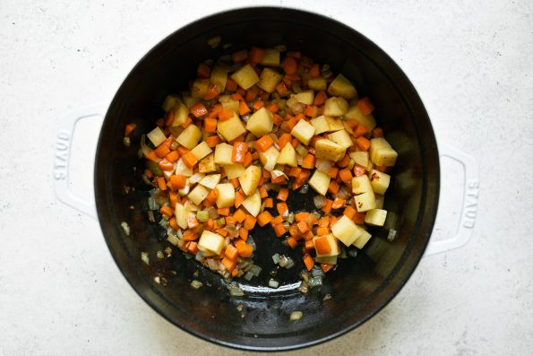 Sauteed veggies (onions, celery, carrot & potatoes) shown in a white Staub Dutch oven placed on a white surface.