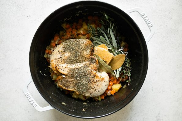 Italian Chicken & Gnocchi Dumplings ingredients (sautéed vegetables, seared chicken breasts, fresh herbs, parmesan rind, bay leaf & Italian seasoning shown in a white Staub Dutch oven placed on a white surface.