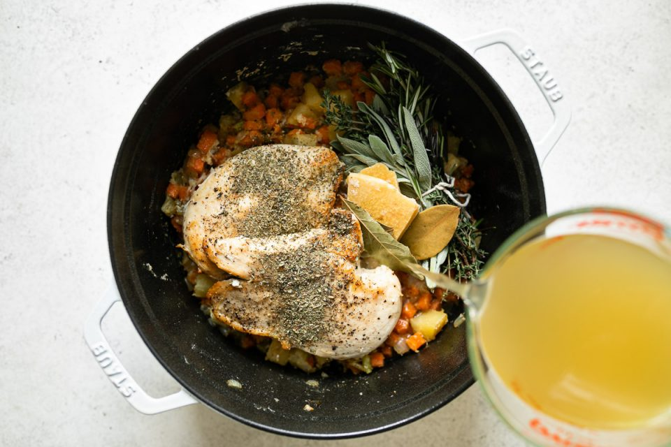 Pouring chicken stock over Italian Chicken & Gnocchi Dumplings ingredients, into a white Staub Dutch oven placed on a white surface.
