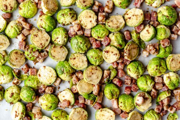 Brussels sprouts coated in Maple syrup & mustard, on a large baking sheet with dice pancetta.