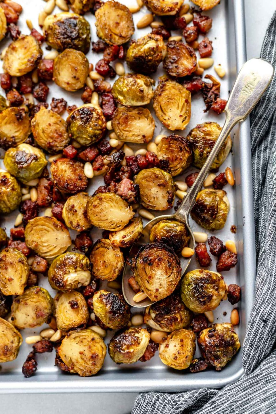 Maple mustard roasted brussels sprouts with pancetta & pine nuts on a large baking sheet. The baking sheet sits atop a light blue surface next to a striped blue linen napkin.