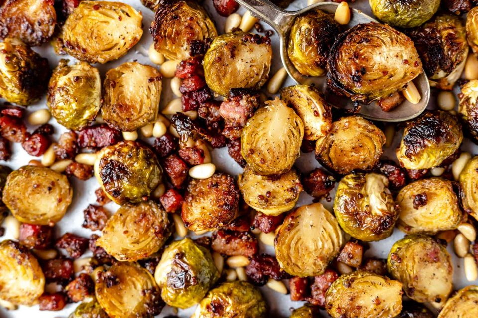 Close view of maple mustard roasted brussels sprouts with pancetta & pine nuts on a large baking sheet.